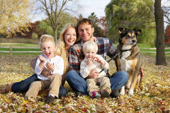Lycklig familj av fyra personer och hunden utanför i höst Fotografering för Bildbyråer