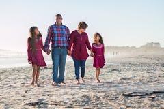 Lycklig familj av fyra som går på stranden som påverkar varandra arkivbild