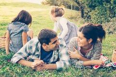 Lycklig familj av fyra som ligger i gräset i höst royaltyfri fotografi