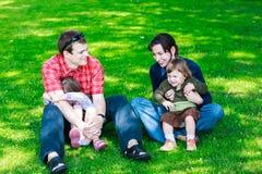 lycklig familj av fyra som sitter på gräs Royaltyfri Fotografi