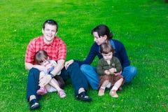 lycklig familj av fyra som sitter på gräs Royaltyfri Foto