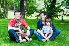 lycklig familj av fyra som sitter på gräs Arkivbild