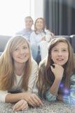 Lycklig familj av hållande ögonen på TV fyra tillsammans hemma Arkivfoton