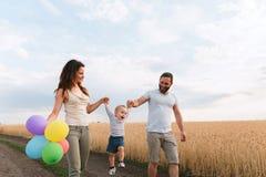 Lycklig familj av mamman, farsan och sonen som utomhus går arkivbild