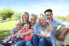 Lycklig familj av 6 som sitter i trädgården Royaltyfri Bild