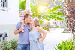 Lycklig familj av tre - den gravida modern, fadern och dottern som kramar och att skratta och att ha gyckel i solnedgången, parke arkivbilder