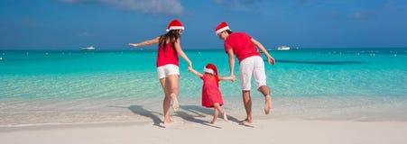 Lycklig familj av tre i julhattar som har gyckel Royaltyfri Foto
