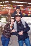 lycklig familj av tre moder, fader och son som ler att skratta, utanför Arkivfoton