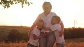 Lycklig familj av tre personer Barn som utomhus spelar med deras föräldrar