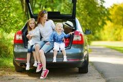 Lycklig familj av tre som går till en bilsemester Royaltyfri Bild