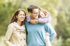 Lycklig familj av tre som har utomhus- gyckel. Royaltyfri Fotografi