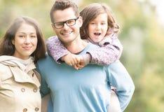 Lycklig familj av tre som har utomhus- gyckel. Arkivfoton