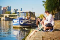 Lycklig familj av tre som sitter på banken av Seinen Arkivfoton