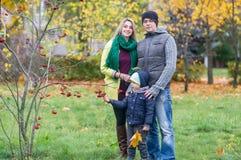 Lycklig familj av tre som tillsammans står i trädgården i höst Royaltyfri Bild