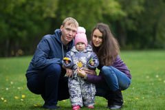 Lycklig familj: Avla, modern och barnet - lilla flickan i höst parkerar: farsan mamma behandla som ett barn att posera som är uto Royaltyfri Fotografi