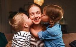 Lycklig familj! Barn kysser mammaafton för läggdags arkivfoton