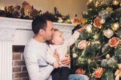 Lycklig familj bland julpynt hemma Arkivbilder