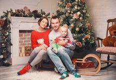 Lycklig familj bland julpynt hemma Arkivbild