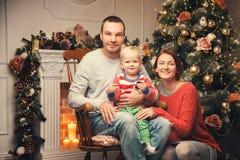 Lycklig familj bland julpynt hemma Royaltyfri Bild
