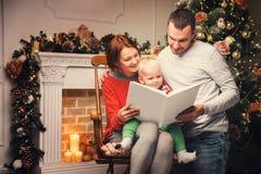 Lycklig familj bland julpynt som läser berättelse i en bok Arkivfoton
