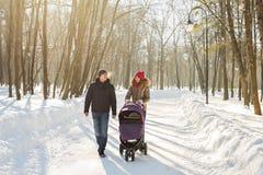 Lycklig familj - den moder-, fader- och barnpojken på en vinter går arkivfoton