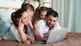 Lycklig familj, föräldrar och två döttrar som håller ögonen på film på bärbara datorn, ultrarapid arkivfilmer