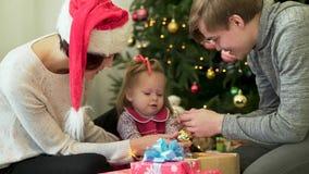 Lycklig familj, föräldrar som framme visar Ney Year garneringar till deras gulliga barn av julgranen Fostra i jultomtenhatt lager videofilmer