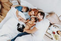 Lycklig familj för bästa sikt som tillsammans sover i säng arkivbild