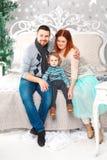 Lycklig familj för jul av tre personer och granträdet med gåvaaskar över vit sovrumbakgrund Arkivfoto