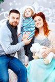 Lycklig familj för jul av tre personer och granträdet med gåvaaskar över vit sovrumbakgrund Arkivbilder