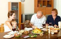 Lycklig familj för tre utvecklingar som äter höna över den stora tabellen Royaltyfria Foton