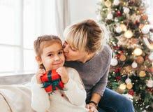 Lycklig familj, farmor och sondotter som sitter nära julgranen arkivfoton