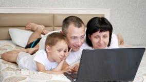 Lycklig familj: farsan mamma och behandla som ett barn ligger på sängen och använder en bärbar dator som ler arkivfilmer
