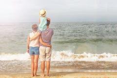 lycklig familj Farsan, modern och dottern står nära havet fotografering för bildbyråer