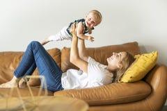 lycklig familj Fostra och behandla som ett barn dotterlekar, på soffan royaltyfria foton