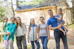 Lycklig familj framme av den gamla ladugården arkivfoto