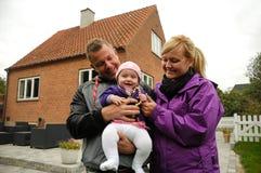Lycklig familj framme av huset Arkivbilder
