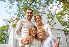 Lycklig familj framme av huset utomhus Arkivfoton