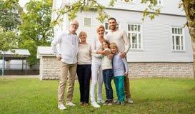 Lycklig familj framme av huset utomhus Royaltyfria Bilder
