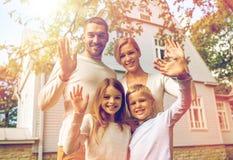 Lycklig familj framme av huset utomhus Royaltyfri Foto