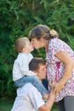 lycklig familj Gravid moder med hennes make och son i parkera Mumen kysser sonen, och buktar den kyssande modern för farsa Arkivfoto
