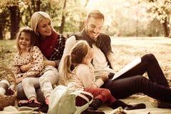 lycklig familj ha picknicken Faderundervisningdotter som ska läsas royaltyfri fotografi