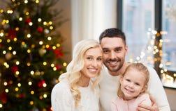Lycklig familj hemma över ljus för julträd arkivbild