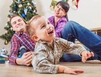 Lycklig familj hemma i jultid Arkivbilder