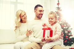 Lycklig familj hemma med julgåvaasken Fotografering för Bildbyråer