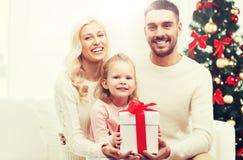 Lycklig familj hemma med julgåvaasken Arkivfoto