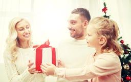 Lycklig familj hemma med julgåvaasken Arkivfoton