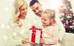 Lycklig familj hemma med julgåvaasken Arkivbild