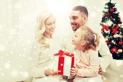 Lycklig familj hemma med julgåvaasken Arkivbilder