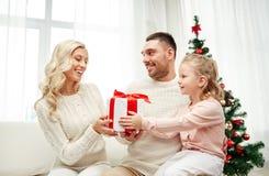 Lycklig familj hemma med julgåvaasken Royaltyfri Fotografi